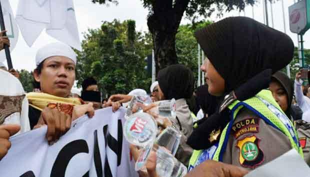 Seorang Polwan saat demo berlangsung membagi-bagikan permen dan minuman kepada pendemo yang akan menuju Istana Negara. [repro internet]